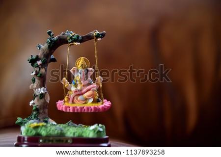Hindu God-Ganesha in art form sitting on a swing. text translation = Jai Ganesha (Hindu god name). Hindu Lord Ganesha, a symbol of success, trouble remover and prosperity