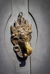 Hindu God Ganesha. Vintage metal door knocker on an gray wooden door, vertical