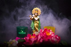 Hindu god Krishna. Statue with a smoke and lotus flowers on a black background