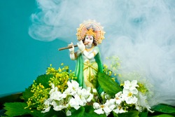 Hindu god Krishna. Statue with flowers and smoke on a blue background.