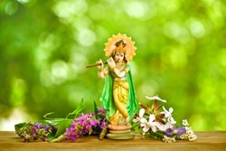 Hindu god Krishna. Statue with fresh flowers on a green bokeh background.