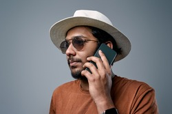Hindu macho dressed in modern clothing with white hat and sunglasses poses in gray background with his mobilephone.
