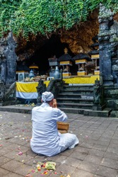 Hindu priest praying at Pura Goa Lawah (