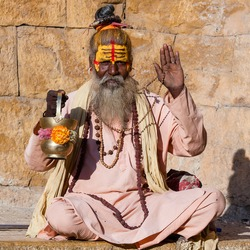 Hindu sadhu holy man, sits on the ghat, seeks alms on the street in Jaisalmer, Rajasthan, India . Close up