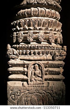 Hindu temple architecture detail. Wooden column with Nepali Hindu God (Vishnu avatar) figure and floral ornament. Nepal, Kathmandu