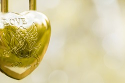 Hinged gold lock in the form of a heart, the inscription love angel with an arrow on a blurred background. Symbol of wedding. Copy space.