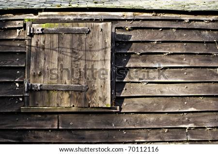 hinged window or door in an old wooden barn