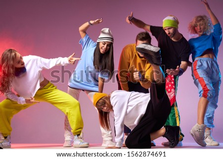 Hip hop battle in spacious dance hall, young people dancing break dance, pretty sportive girl in white hoodie and black loose pants showing street dance movie