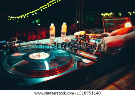 Hip hop concert dj scratches vinyl record with music on stage.Professional disc jockey mixes musical tracks on summer festival outdoor.Retro djs turn table player & sound mixer deck on scene in club