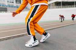 Hip hop dancer in bright clothes dancing on the stadium sports track,close up photo of legs.Legs of young man in orange pants dancing hip hop on sports track against roller skates.Background.Сopyspace