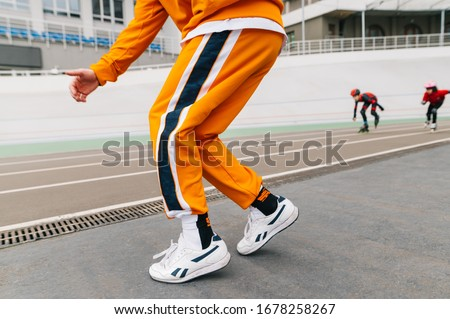 Hip hop dancer in bright clothes dancing on the stadium sports track,close up photo of legs.Legs of young man in orange pants dancing hip hop on sports track against roller skates.Background.Сopyspace Stock fotó ©