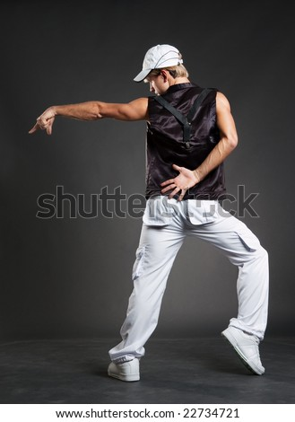 hip-hop dancer in dance pointing against dark background