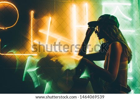 Hip-hop girl in cap in neon light. Fashion portrait of modern young woman in cap and sunglasses.