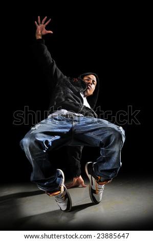 Hip hop man dancing over a dark background