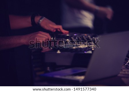 Hip hop party dj scratching turntables disc.Professional disc jockey mixing musical tracks with digital cd player turn table on stage in night club.Performing arts event in music hall