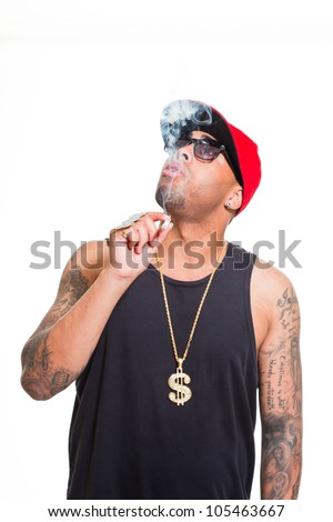 Hip hop urban gangster black man wearing cap, dark shirt and golden jewelry isolated on white. Smoking cigarette. Looking confident. Cool guy. Studio shot.