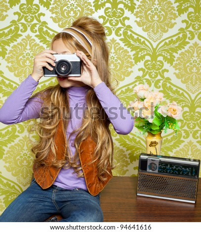 hip retro little girl shooting photo with vintage camera on wallpaper