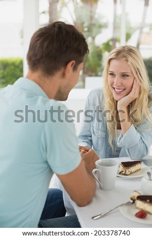 Hip young couple having coffee together on the cafe terrace on sunny day