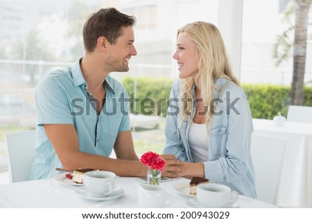 Hip young couple having desert and coffee together on the cafe terrace on sunny day
