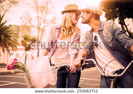 Hip young couple on a bike ride on a sunny day in the city stock photo