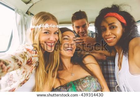 Hippie friends having fun into a vintage van, taking nice pictures