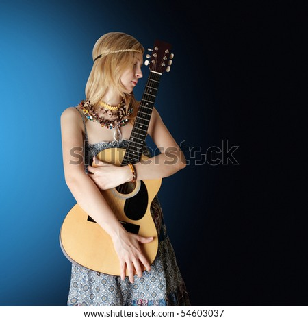 hippie girl with the guitar in blue studio