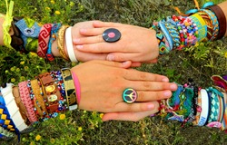 Hippie style friends girls hold hands with handmade bracelets, baubles and rings. Boho fashion