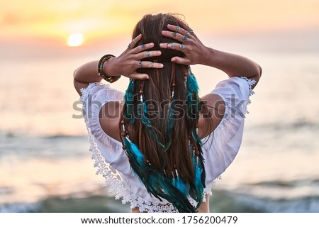 Hippie woman wearing blue feathers in long hair, silver rings with stone and white blouse stands back at sunset. Indie boho vibes and bohemian style