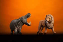 hippopotamus and lion toys, isolated on orange background