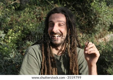 hippy preparing, rolling and smoking marijuana joint : photos series - stock photo