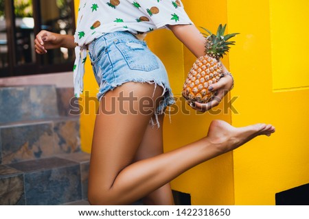 hips in jeans shorts of attractive woman on summer vacation, skinny figure sexy body, holding pineapple, fruit diet detox, tanned skin, yellow background