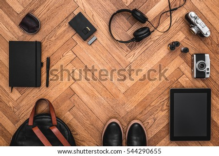 Hipster, artist items on wooden floor. Top view of photography stuff with cameras, backpack, tablet on wooden floor. Copy space. View from above. Flat lay.