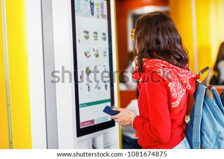 Hipster asian woman orders food at the touch screen self service machine by the electronic menu in the fastfood restaurant