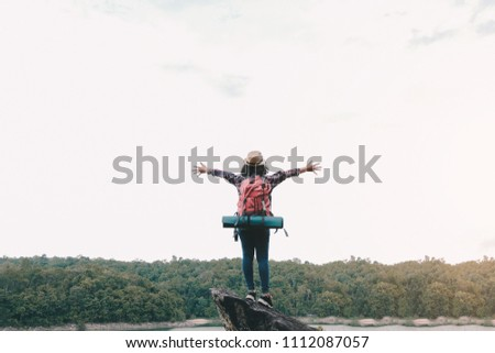5b8bb97633 Hipster asian young girl with backpack enjoying sunset on peak mountain.  Travel Lifestyle adventure concept