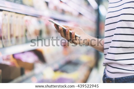 Hipster at grocery using smartphone. Young woman shopping healthy food in supermarket blur background. Close up view girl buy products using smartphone in store. Person comparing the price of produce
