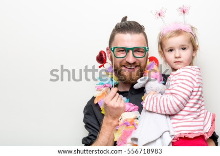 hipster beard guy with little baby girl daughter  in photo booth with floral props separated on white background #556718983