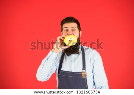 Hipster bearded baker hold glazed donut on red background. True facts about sugar. No way. Cafe and bakery concept. Sweet donut from baker. Man bearded baker in cooking apron hold cute dessert. #1321605734