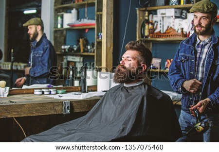 Hipster bearded client got hairstyle. Barber with hairdryer blows off hair out of cape. Barber with hairdryer works on hairstyle for bearded man, barbershop background. Barbershop concept.