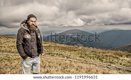 hipster. bearded man, long beard. brutal caucasian with moustache. unshaven guy in jacket with stylish hair getting beards haircut mountain top on natural cloudy sky. Bearded man with long beard.