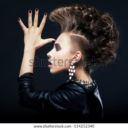 Hipster. Beauty woman with styling pigtails - iroquois, creative hairstyle, saluting Isolated on black
