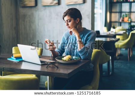 Hipster blogger chatting online on modern smartphone during dinner in coffee shop.Young woman reading news on website on telephone sitting at laptop computer in cafe interior using 4G internet