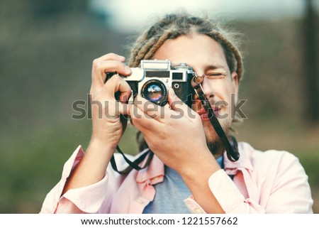 Hipster blonde bearded photograph boy with dreads taking pictures on the nature location in the forest, outdoor view