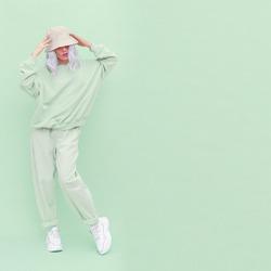 Hipster blonde girl posing in studio. Urban style. Hip-hop. Fresh fashion  monochrome aesthetic colours. Aqua menthe trend
