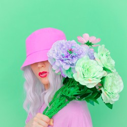 Hipster Blonde with flowers in trendy bucket hat. Fresh summer vibes. Pastel colours lovers