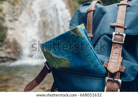Hipster Blue Backpack, And Map Closeup. View From Front Tourist Traveler Bag On Waterfall Background. Exploring Adventure Hiking Concept