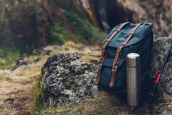 Hipster Blue Backpack, Thermos And Trekking Poles Closeup, Front View. Tourist Traveler Bag On Rocks Background. Adventure Hiking Outdoor Concept