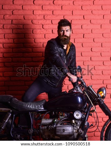 Hipster, brutal biker on serious face in leather jacket gets on motorcycle. Man with beard, biker in leather jacket near motor bike in garage, brick wall background. Masculine passion concept #1090500518