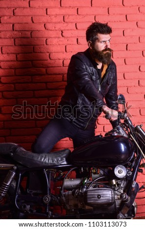 Hipster, brutal biker on serious face in leather jacket gets on motorcycle. Masculine passion concept. Man with beard, biker in leather jacket near motor bike in garage, brick wall background. #1103113073