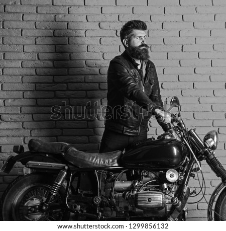 Hipster, brutal biker on serious face in leather jacket gets on motorcycle. Start of journey concept. Man with beard, biker in leather jacket near motor bike in garage, brick wall background. #1299856132