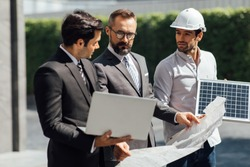 Hipster business man and Office building owner and energy engineer plan a project to build a solar panel for the building under construction. clean and green alternative energy concept.